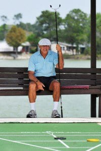 Senior man sitting on a bench with cue in hand, waiting for his turn at shuffleboard.