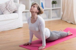 Active senior woman exercising yoga in the morning